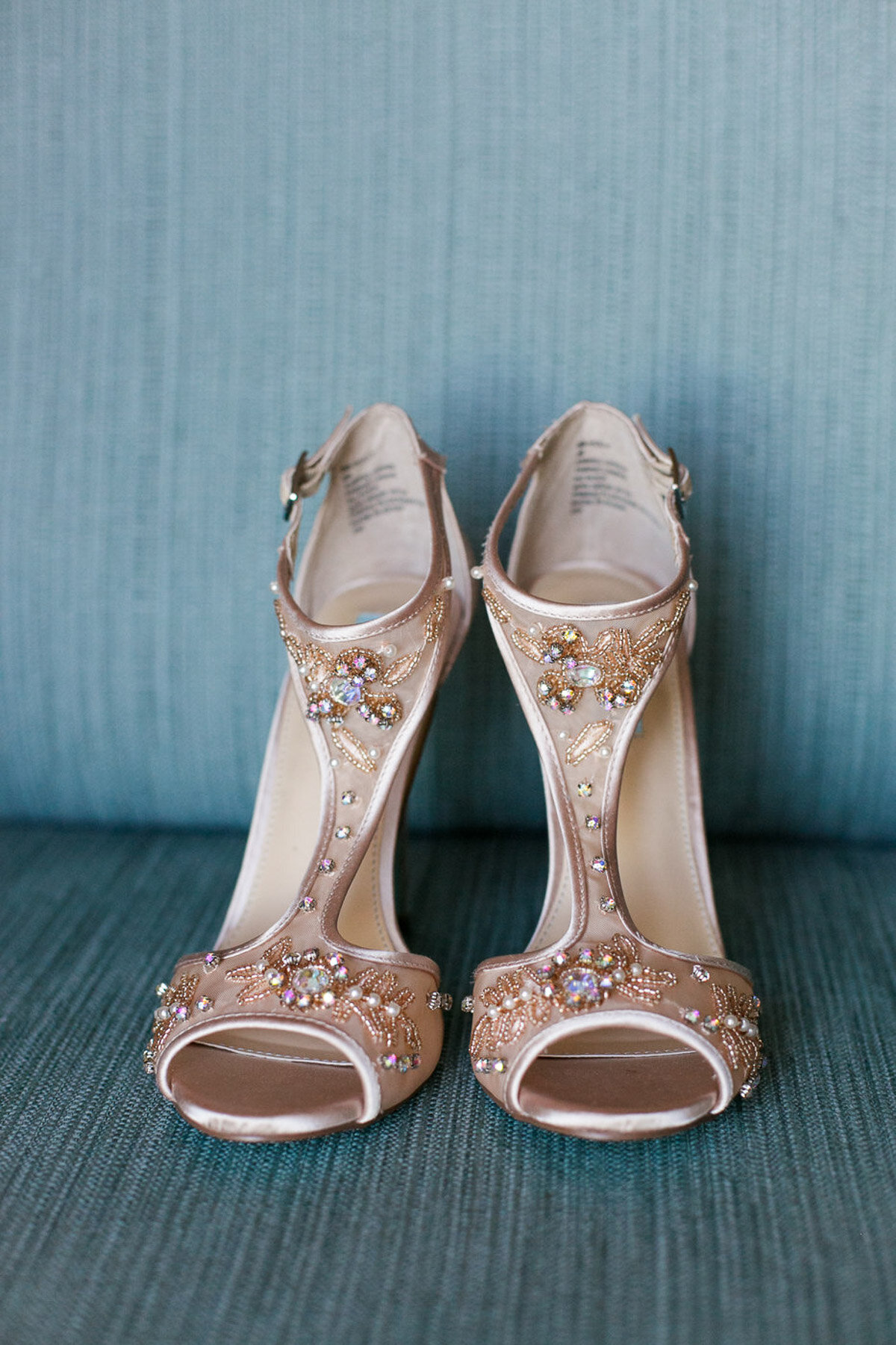 pink weddings shoes on blue sofa