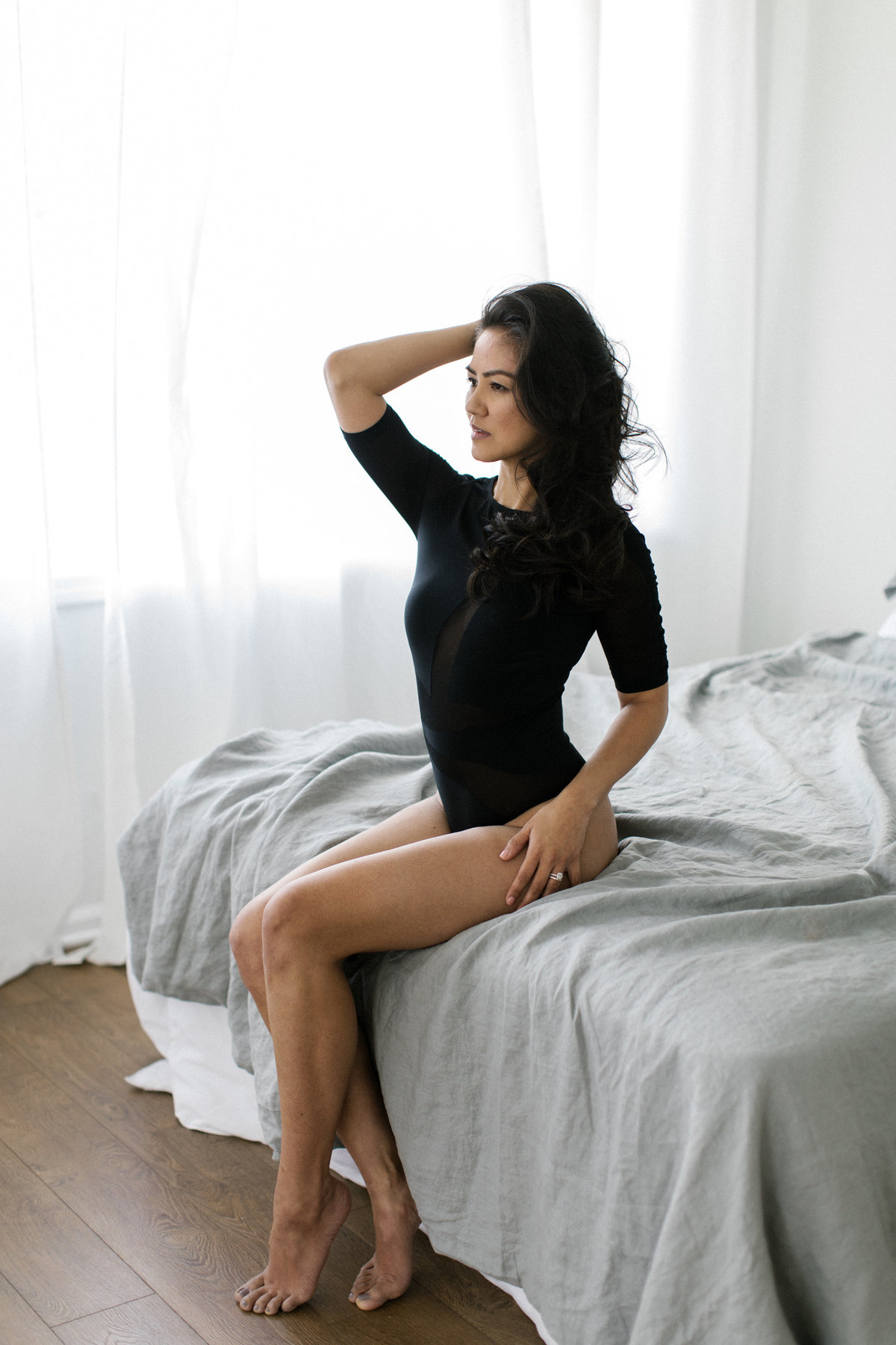 forty and fabulous woman in black one piece sitting on bed