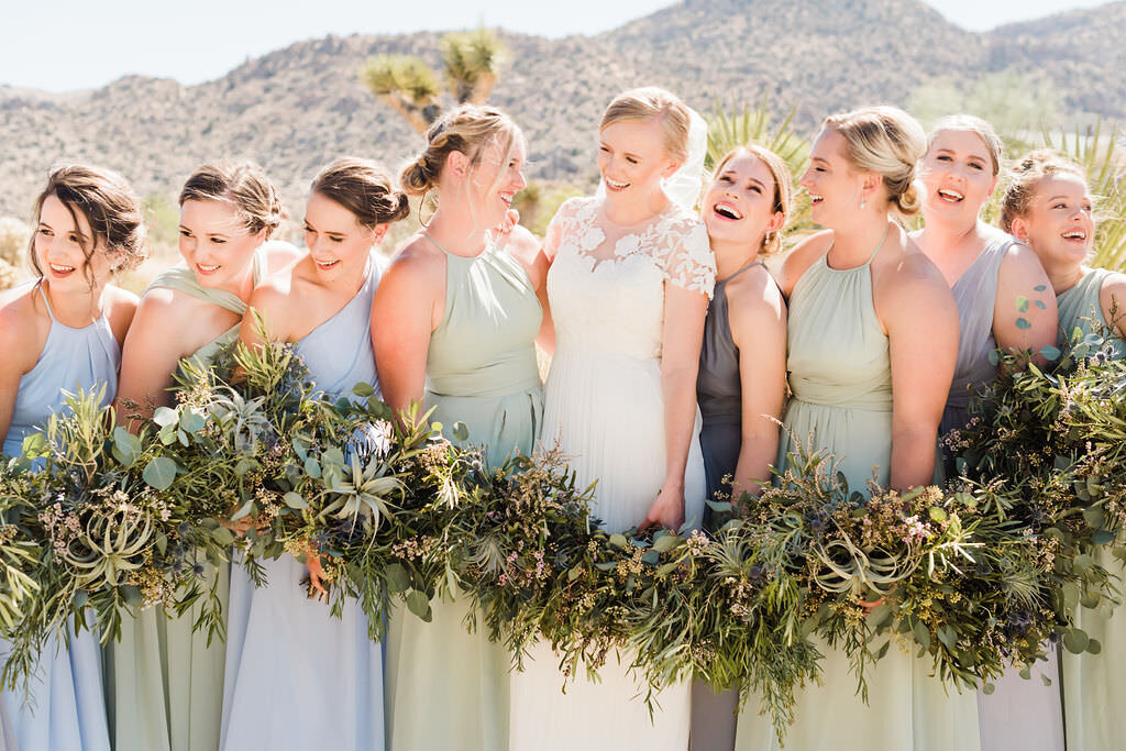 Bride surrounded by her bridal party laughing and holding succulent bouquets in the desert on her wedding day