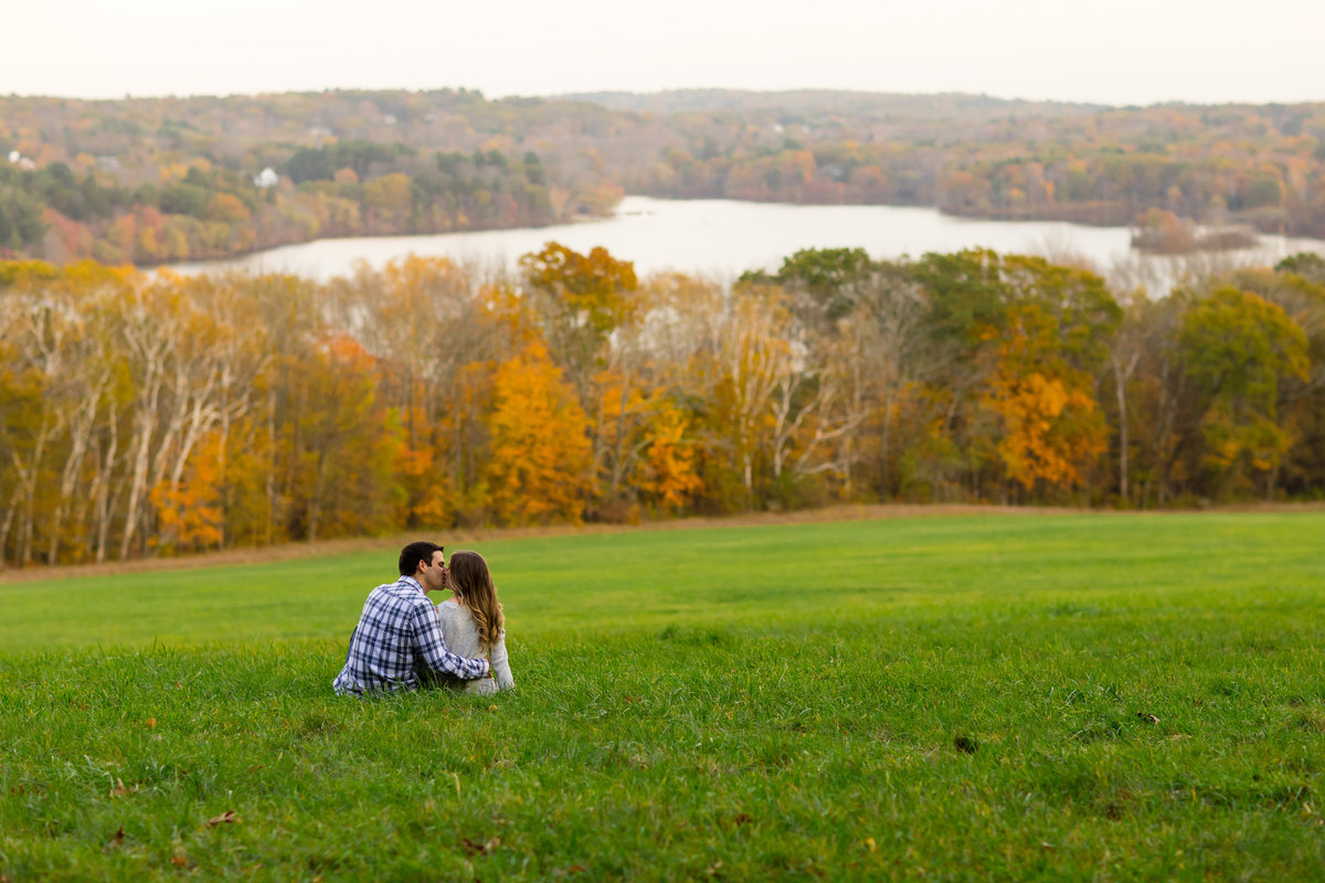 The couple kiss in front of the fall setting way up on a hill in Tamworth NH