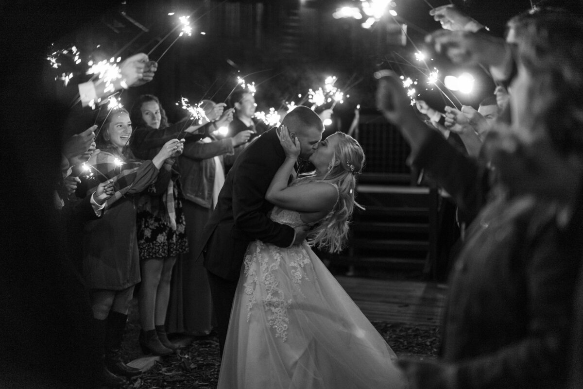 Bride and groom embrace for final kiss underneath sparkler exit at their wedding