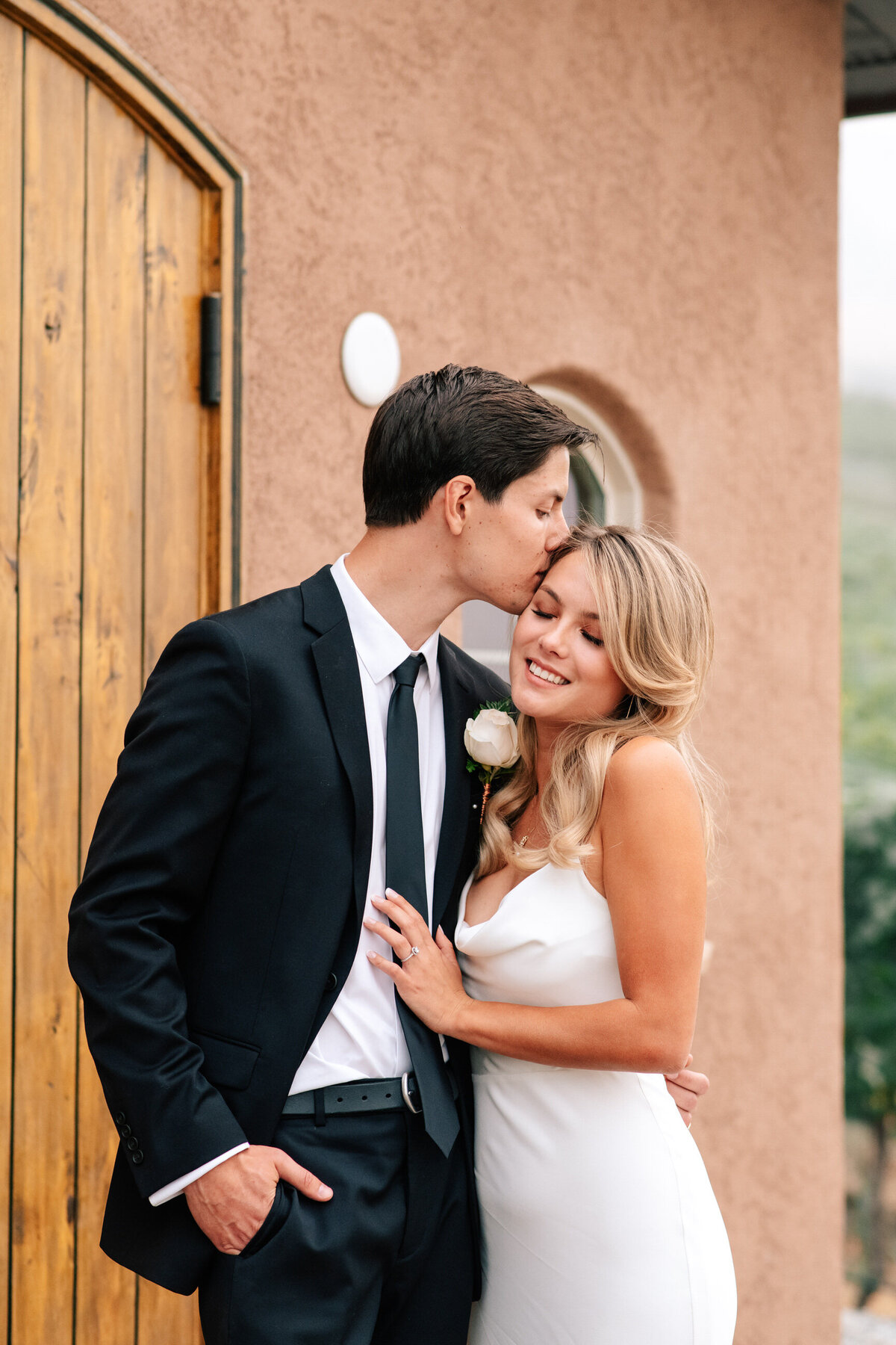 Groom kissing bride's forehead at Tsillan Cellars winery in Chelan, WA