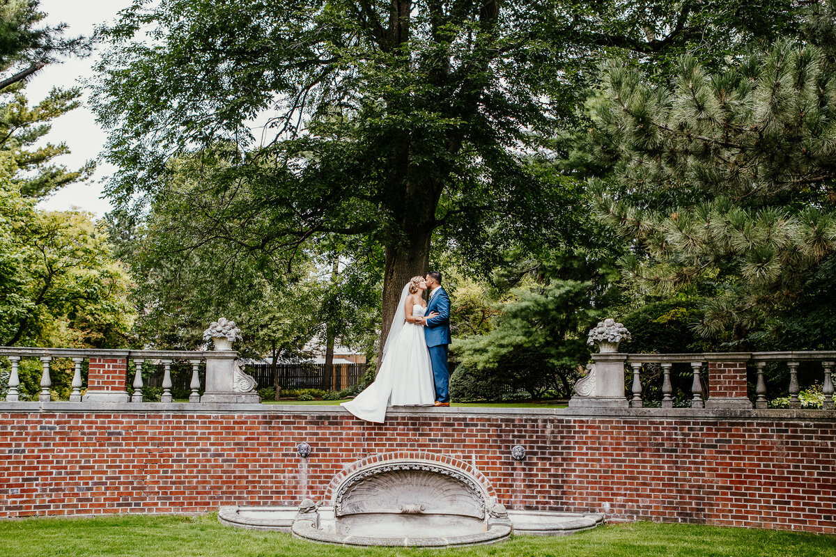 Bride and Groom kissing outside on a wall in Buffalo, New York