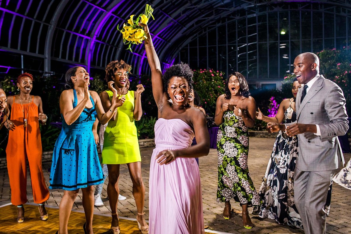A bridesmaid reacts to catching a bouquet at a Garfield Park Conservatory wedding.