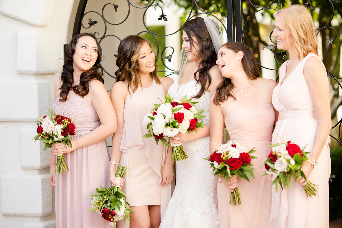 Bride and her bridesmaids in pink and blush dresses share a laugh in the villa de amore courtyard by matty fran photography
