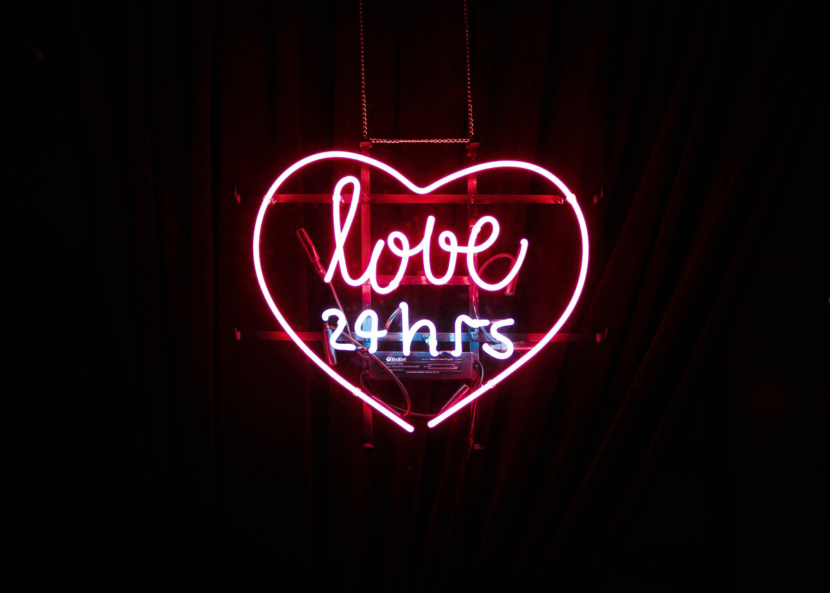 Heart shaped pink neon sign saying love 24hrs.