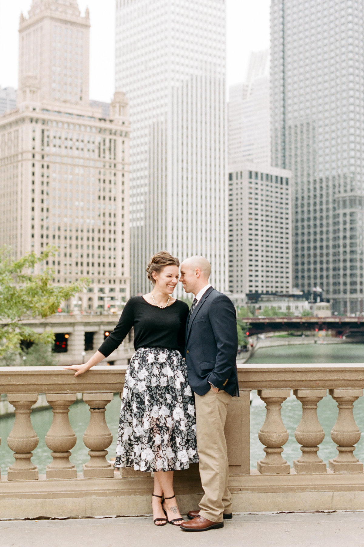 engaged couple standing in downtown chicago whispering to each other