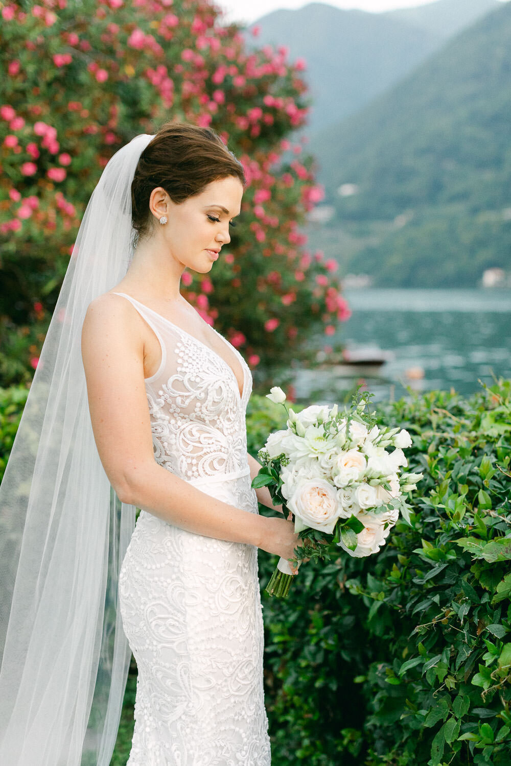 Bride in white lace bridal dress and veil holding white floral bouquet by Lake Como Wedding Italy