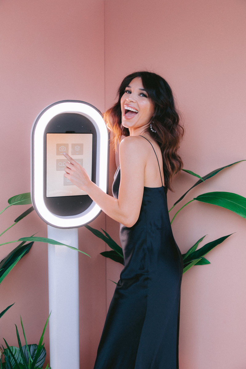 A woman using a photobooth smiling at the camera.