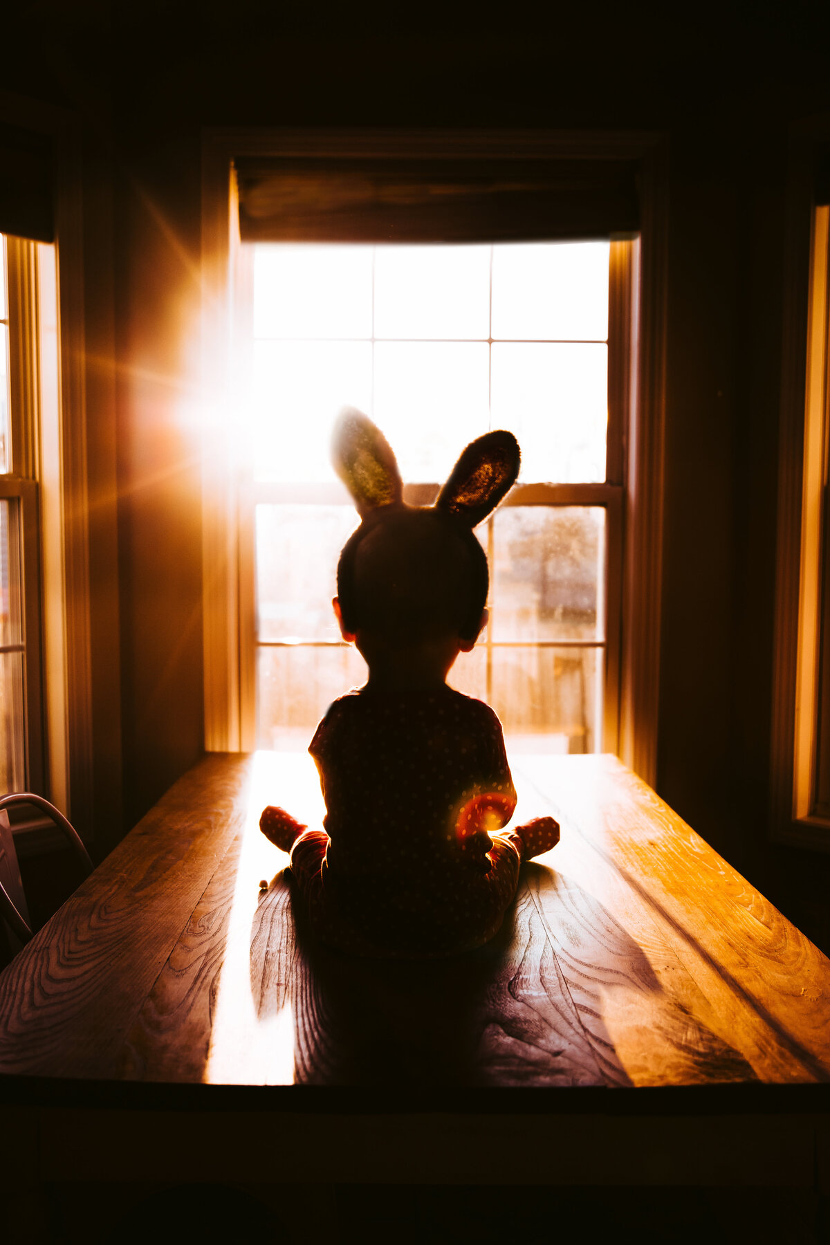 silhouette of baby sitting on table  with bunny ears on