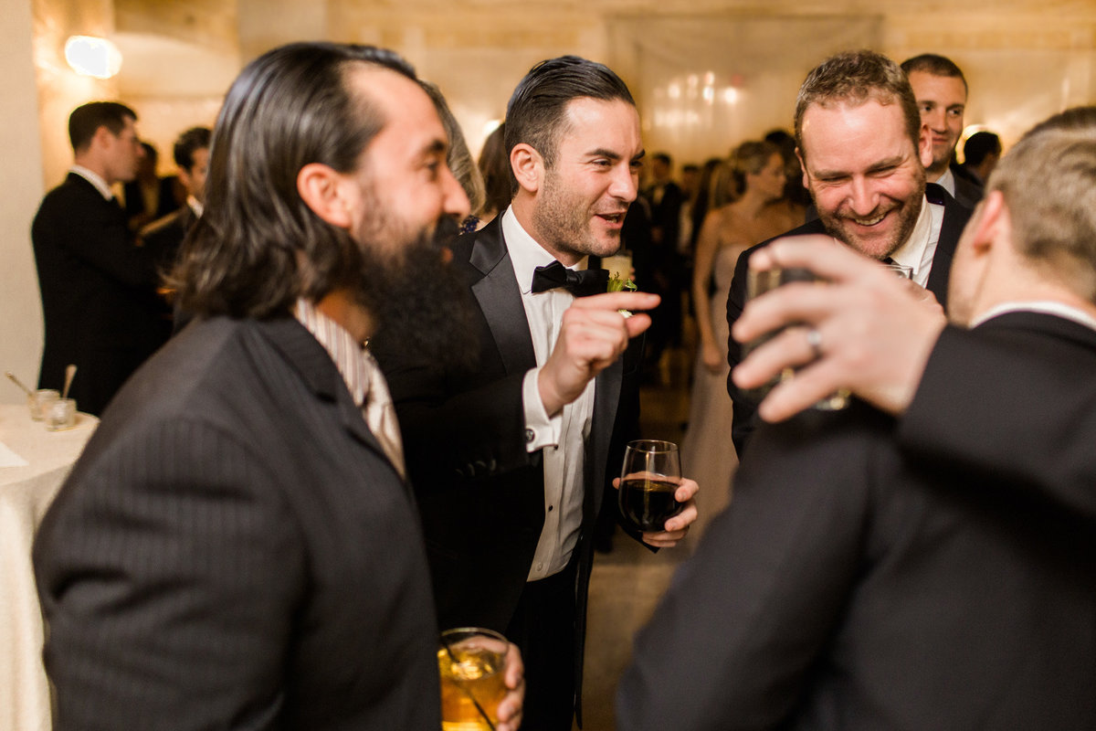 Gentlemen enjoy each other at this black tie cocktail hour at the Biltmore Ballrooms.  Luxury wedding photography by Rebecca Cerasani.
