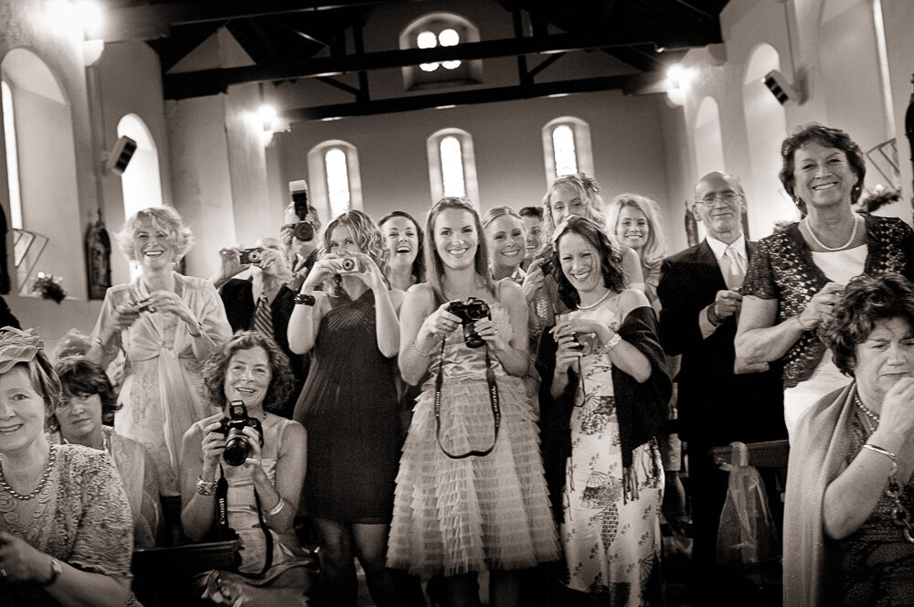 large group of wedding guests taking photographs in Kenmare church