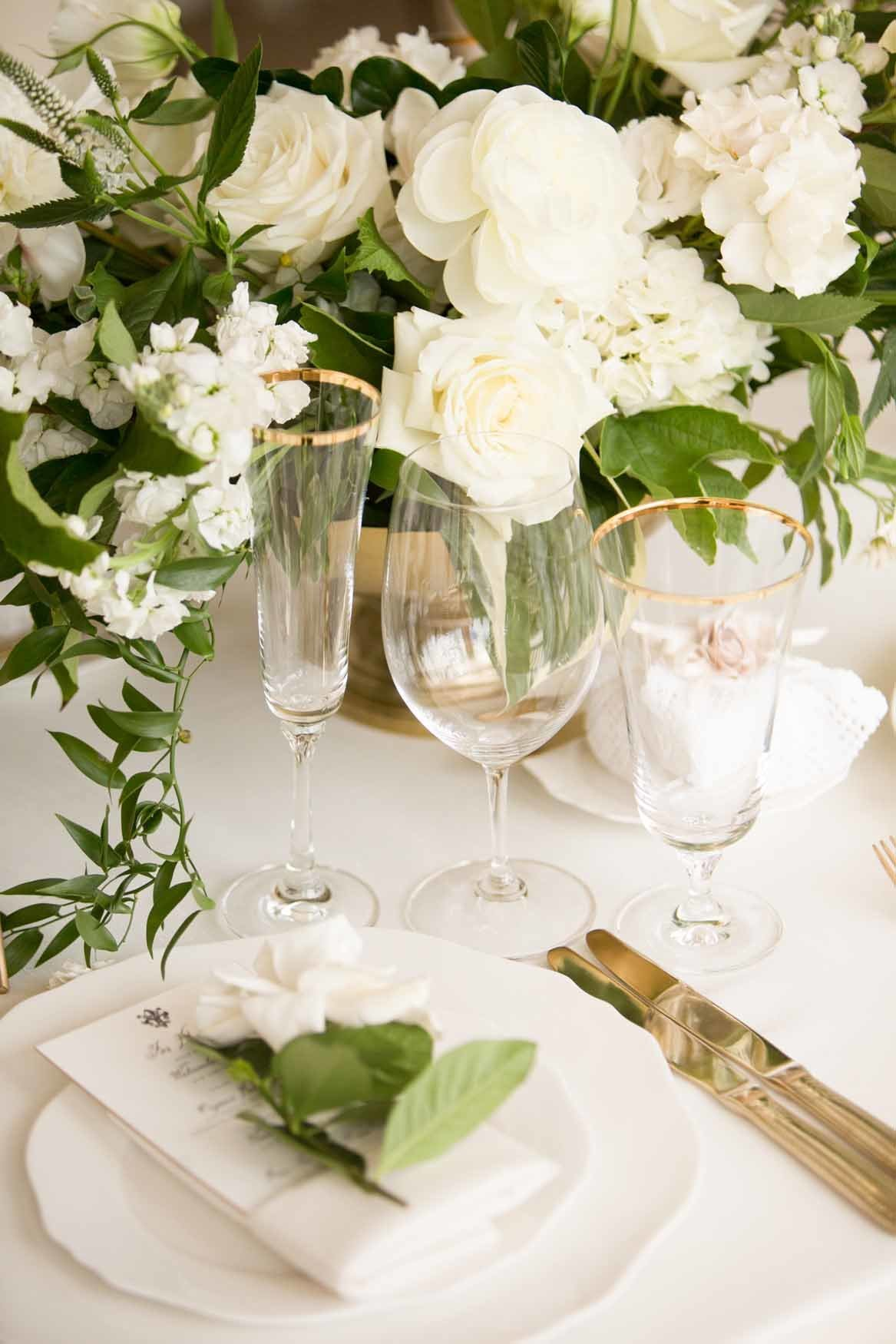 Luxurious white and gold table setting with gardenia napkin flower