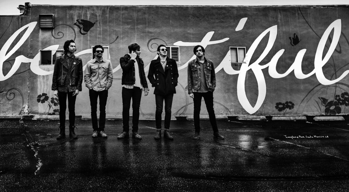 Band portrait panorama format five members Terraplane Sun standing in front of wall with the word beautiful painted on it in script black and white image
