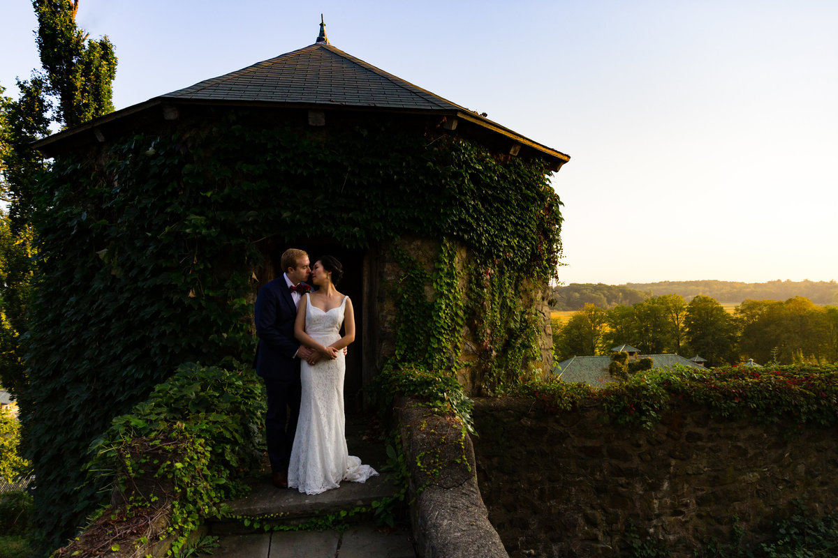 The Barn at Crane Estate wedding venue serves as a gorgeous backdrop for this kissing couple at sunset