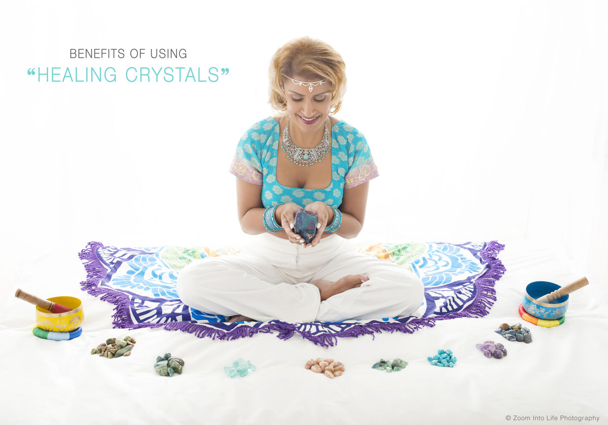 yagoa and  meditation coach sitting on teh  floor  with  holding crystal in her hands meditating  with a smile