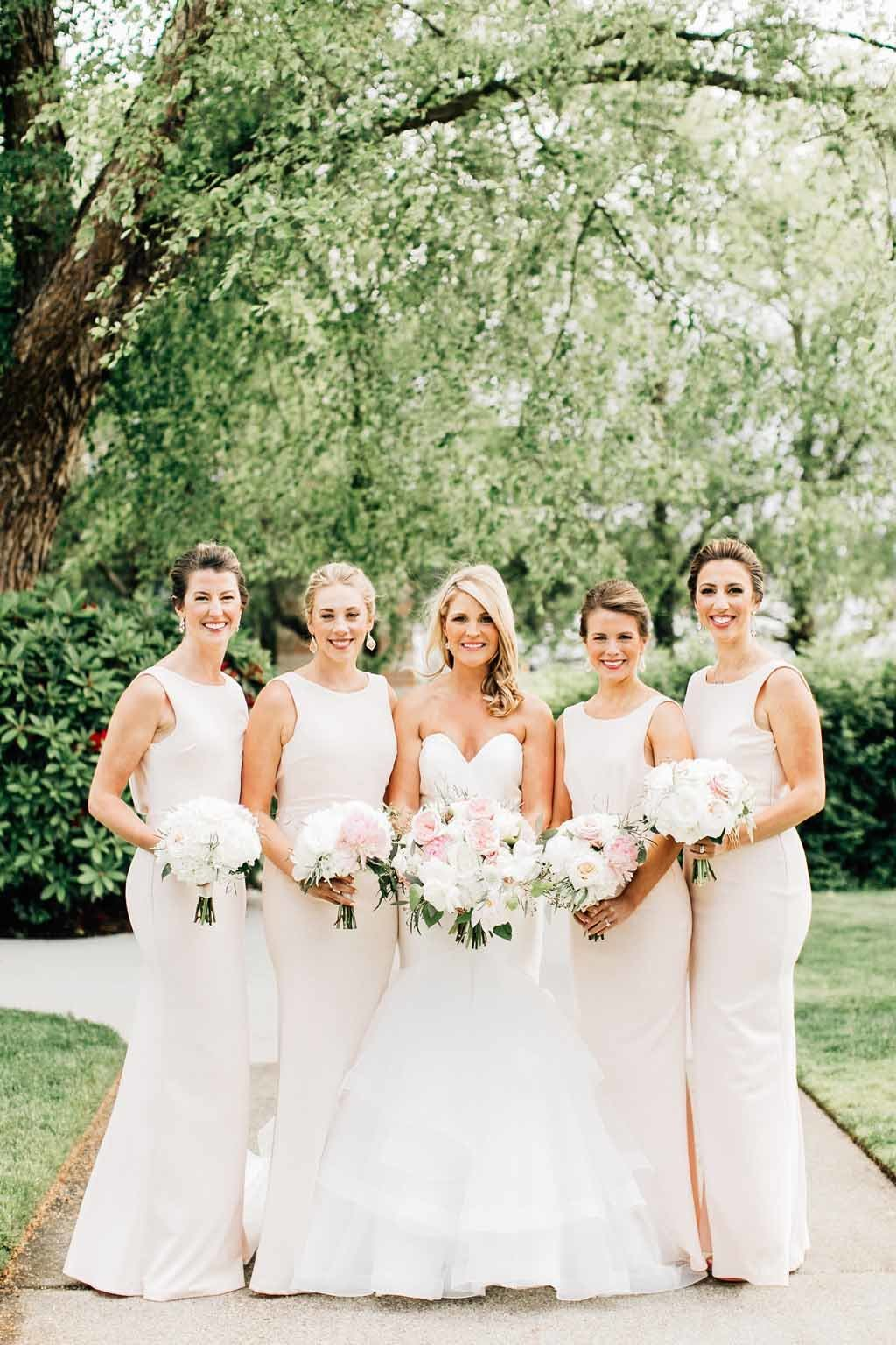 Elegant bridal party dressed in all white with white and blush bouquets.