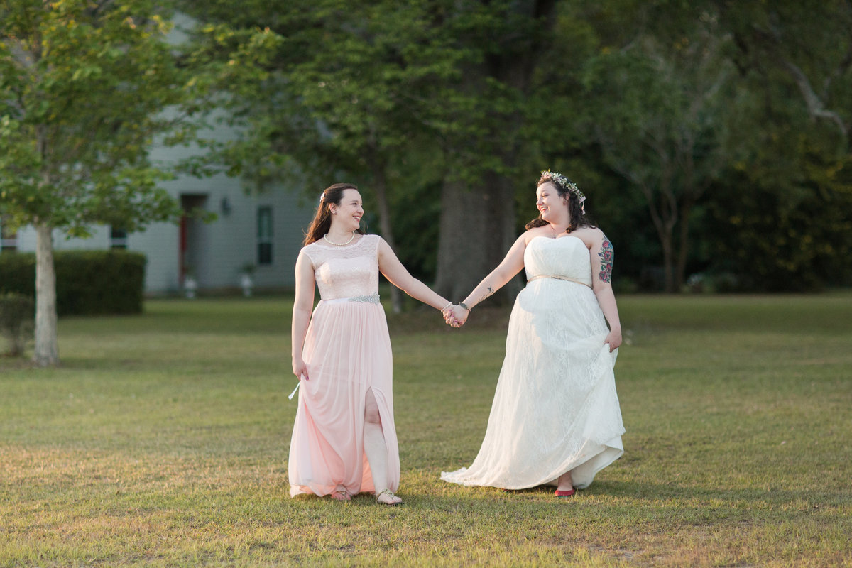 Brides walking hand in hand in warm sunset light