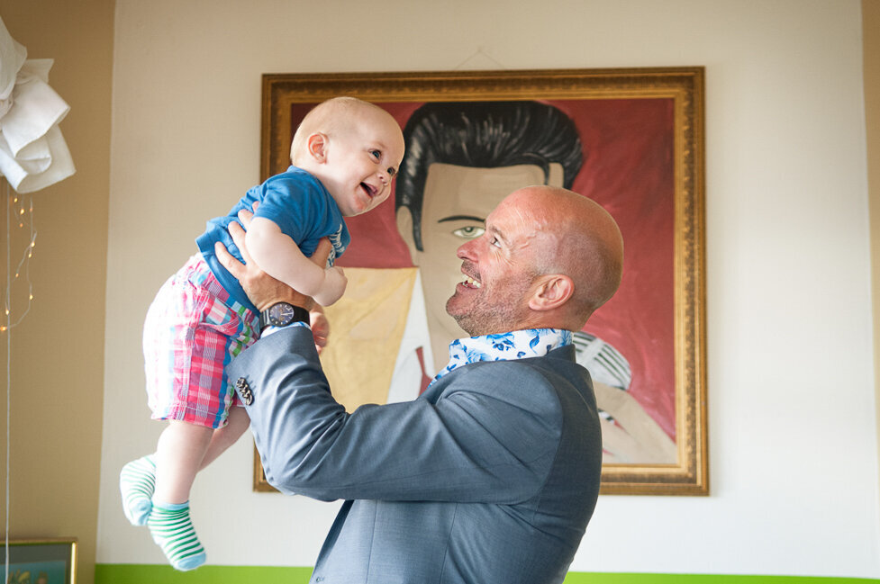 groom wearing a light blue jacket and floral shirt holding his baby son in the air laughing in front of an Elvis portrait in Inch beach cafe