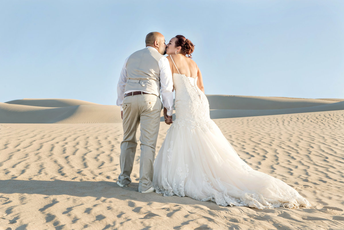 bride and groom kissing on dune at sand dune in Imperial California