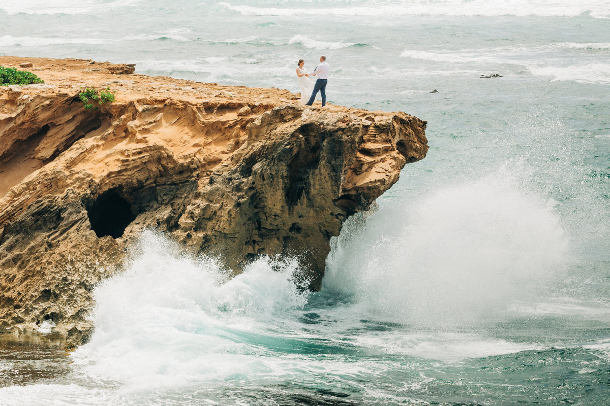 wedding couple on cliff over ocean with wave crashing below