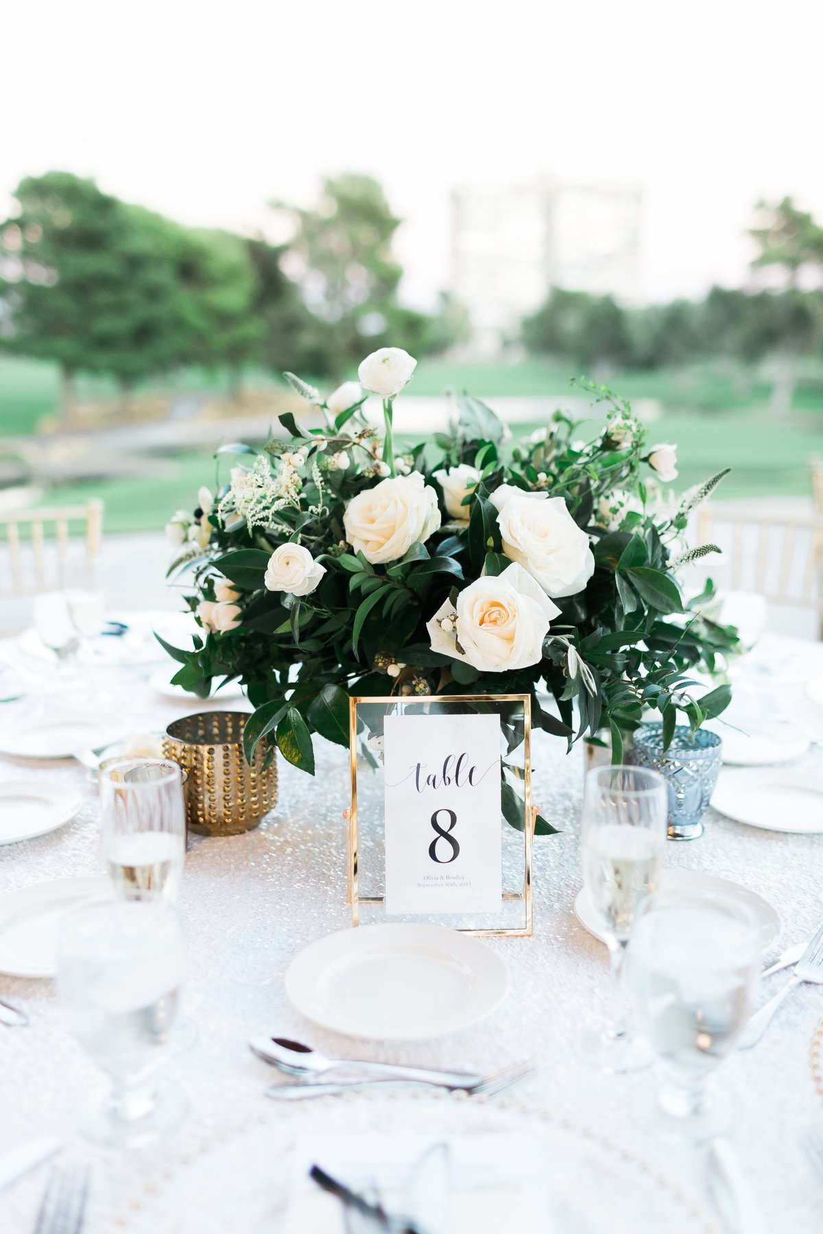 white and greenery centerpiece with gold framed table number