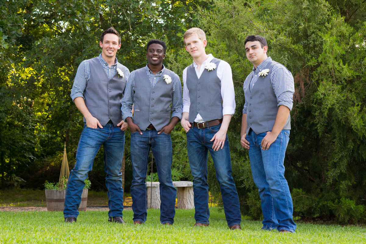 Groom and best men in grey vests and boots looking cool
