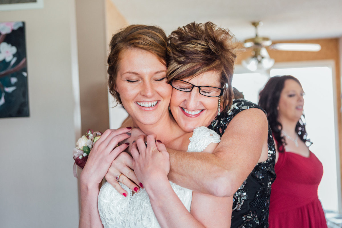 Mom hugging bride on wedding day