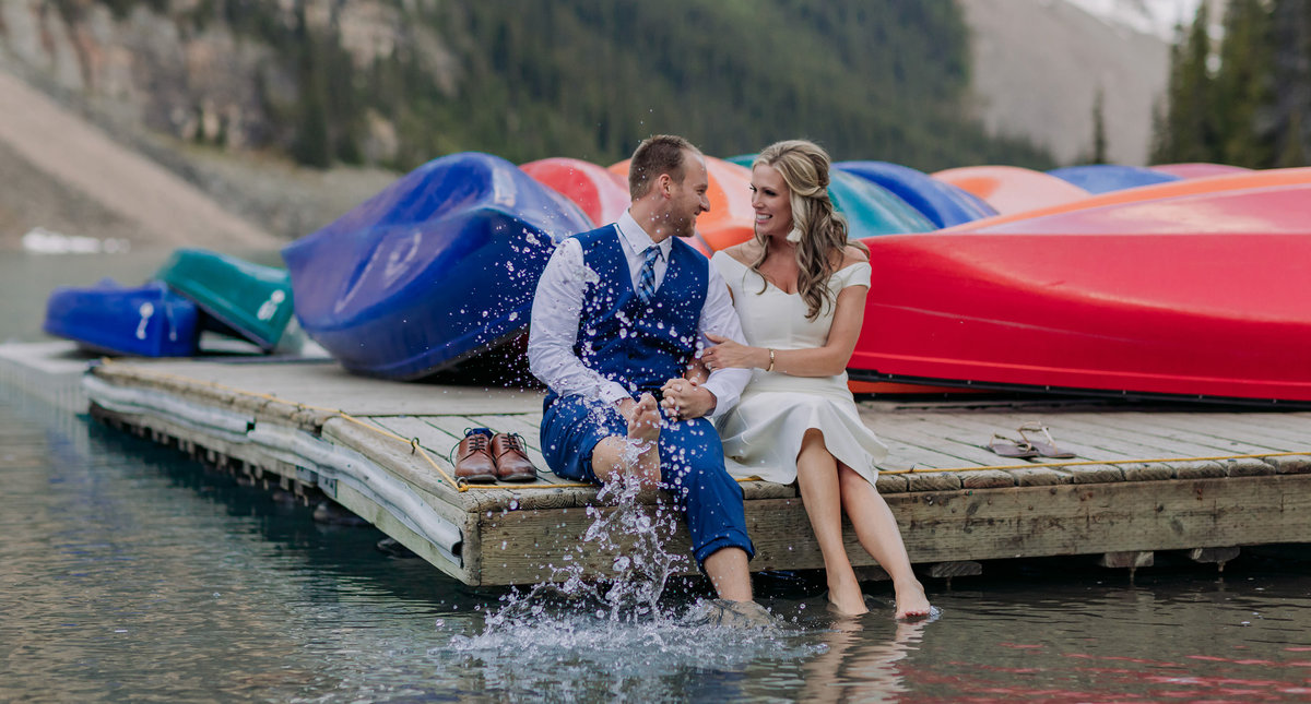 moraine lake elopement playful groom splashing bride lake canoes