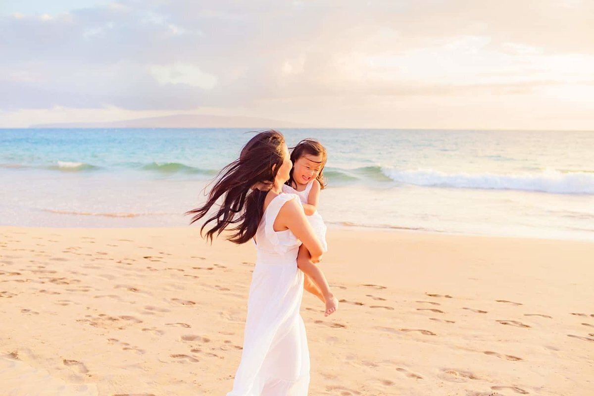 Mother holds her daughter during family portraits on Maui at the beach