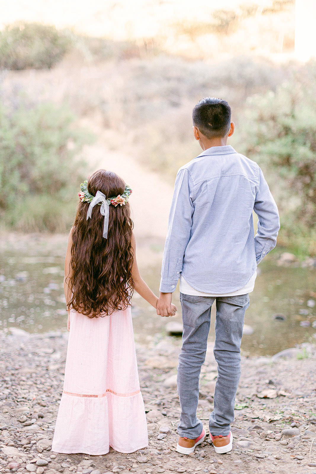 siblings holding hands looking at river