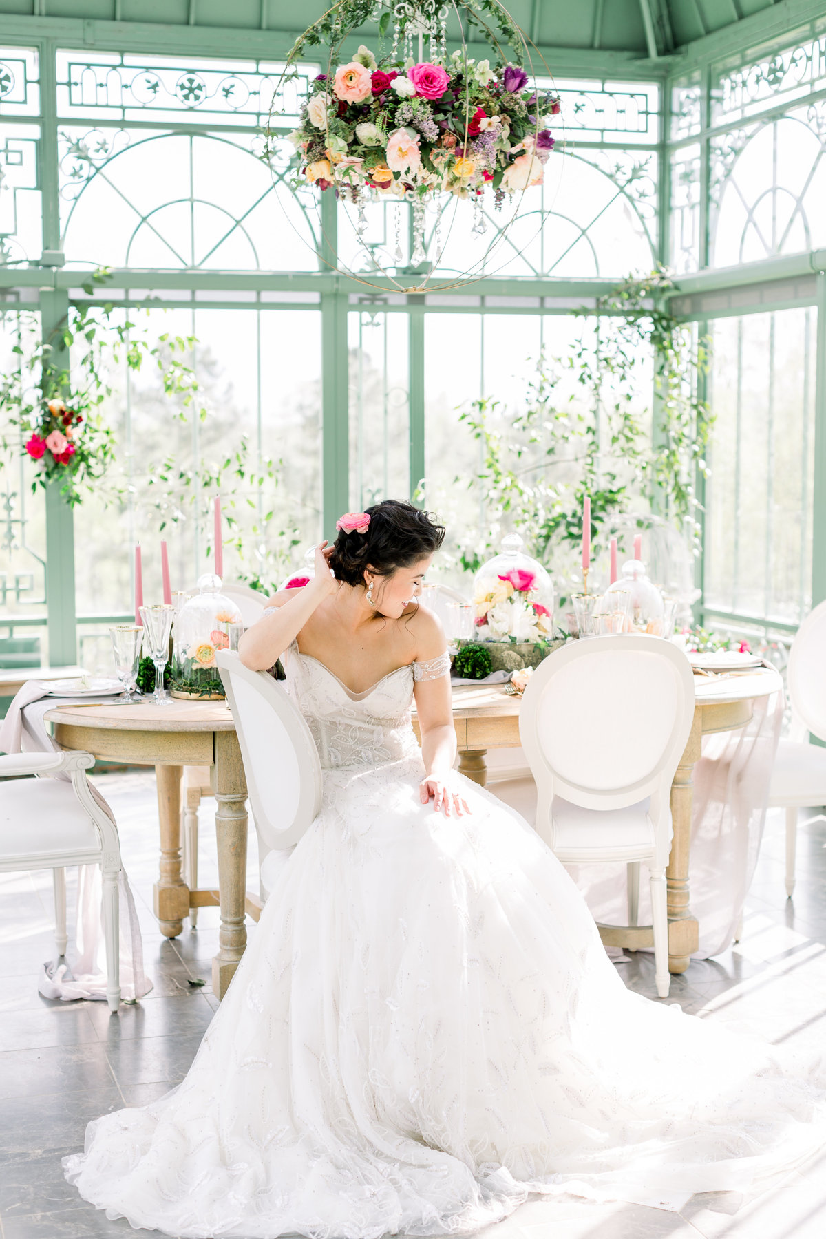 Georgia bride sits at garden wedding table in greenhouse at 6400 on the River