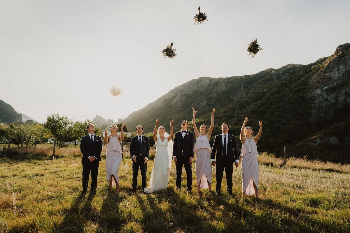 bridal party throwing bouquets in the air