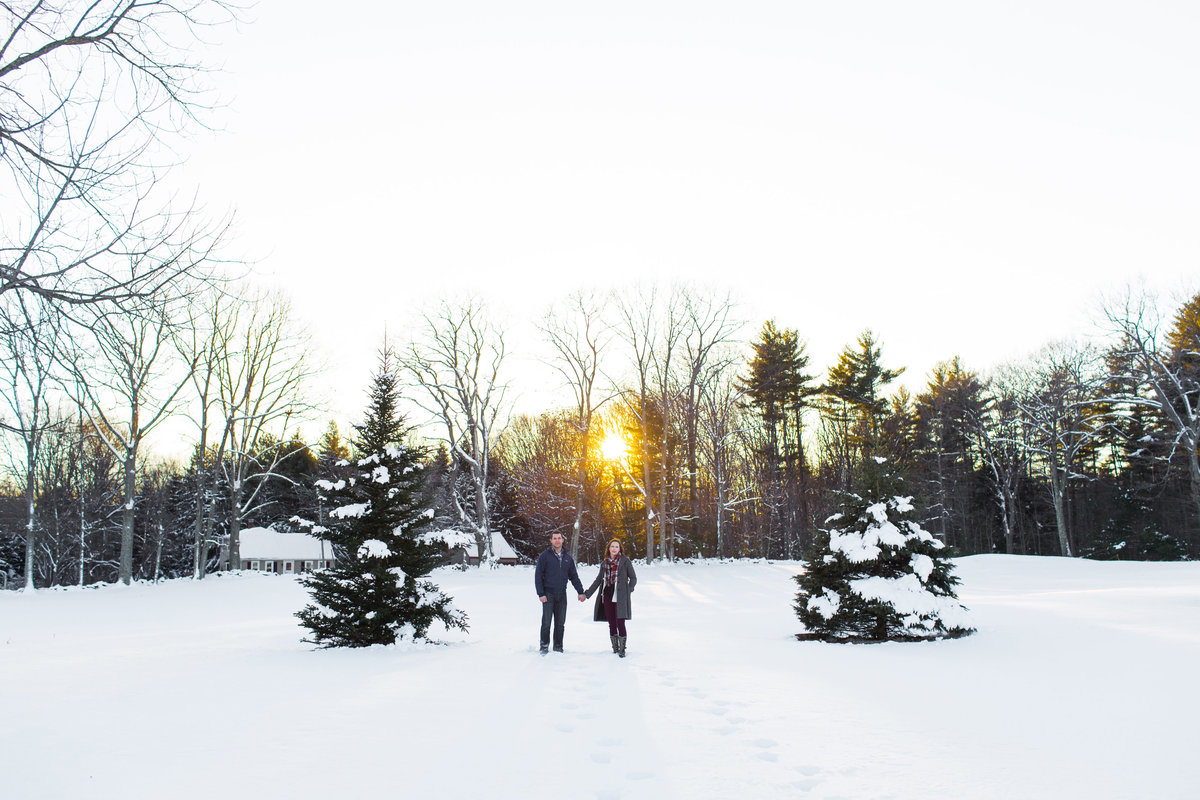 Couple stands in the deep snow in Newmarket NH as the sun sets behind them