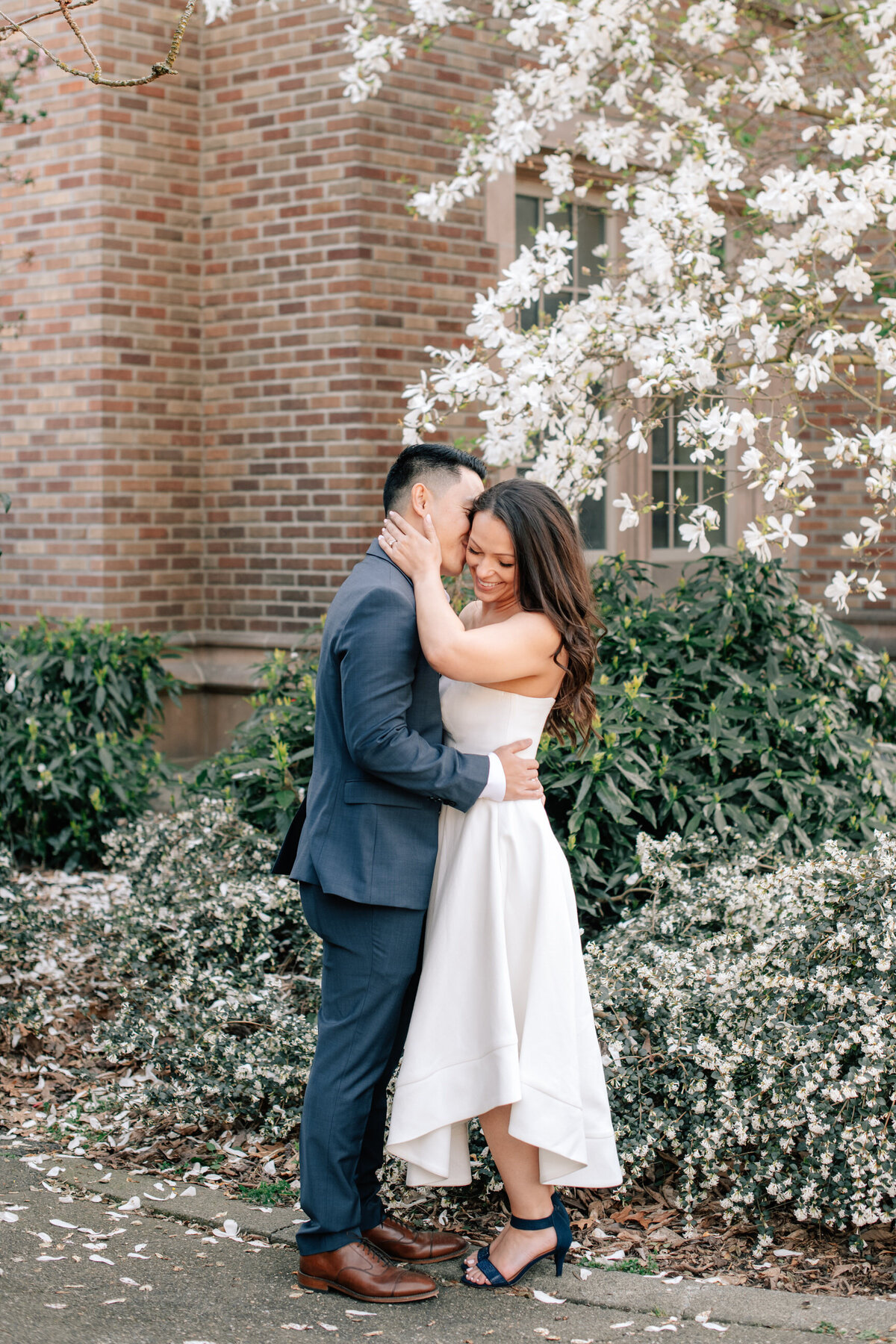 Groom kissing bride on cheek during spring engagement at UW