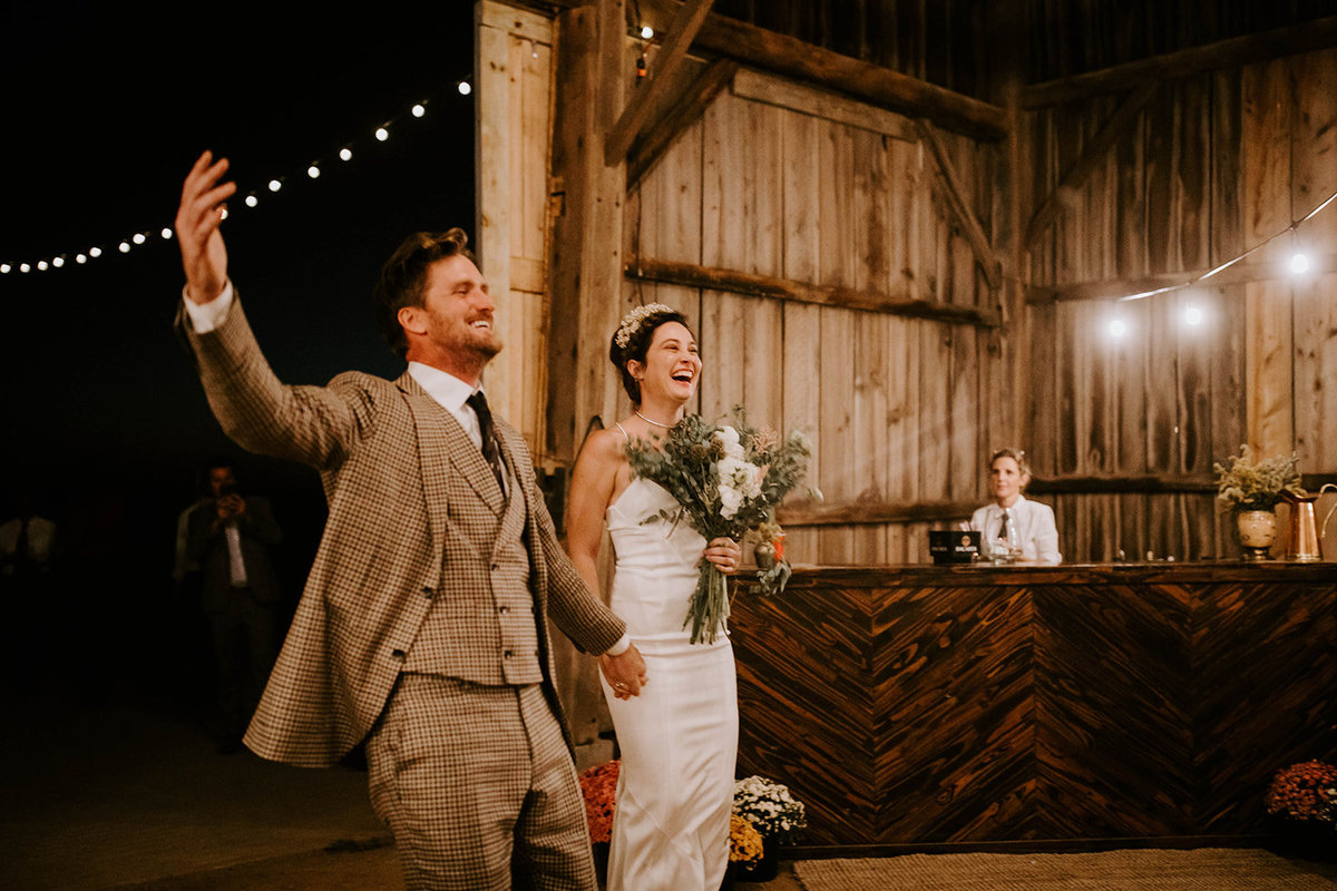 A bride and groom enter their reception in a barn.