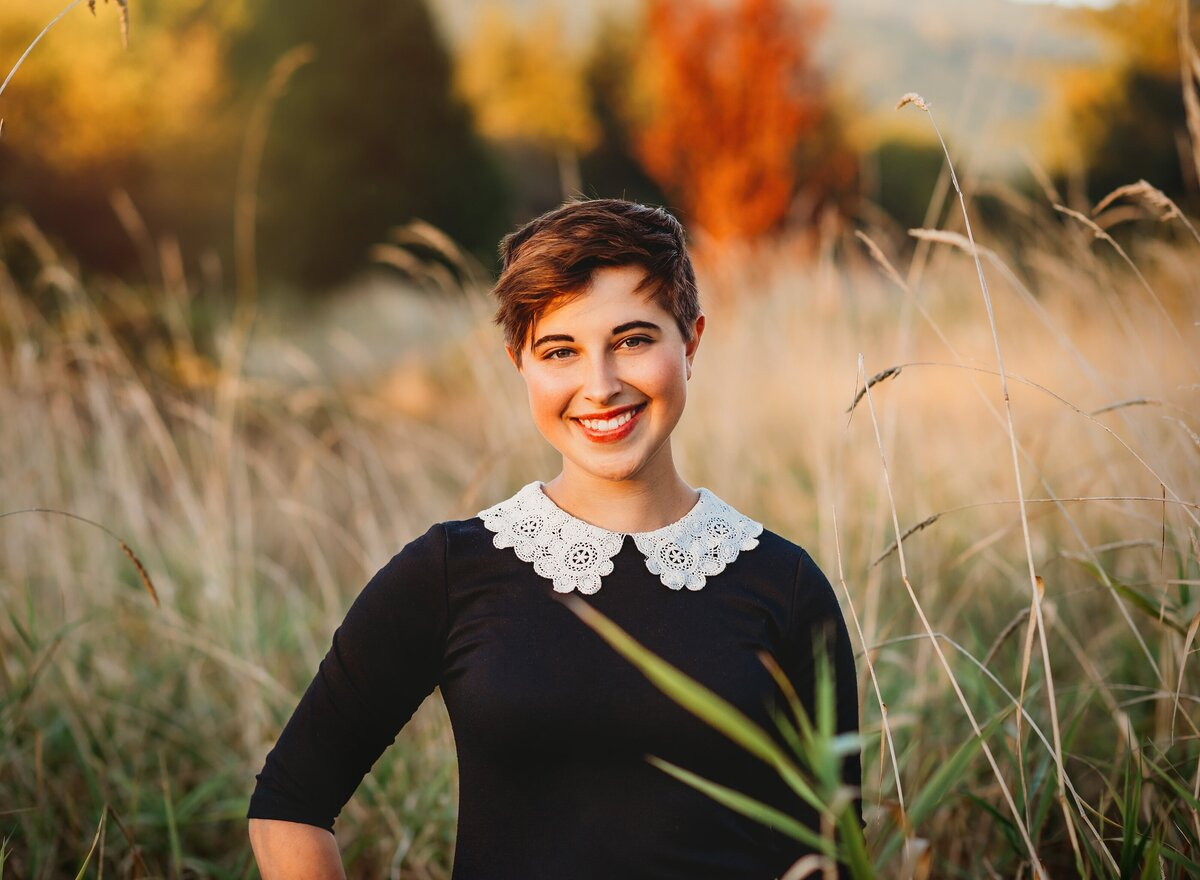 Teen girl smiles for senior portrait in field of tall grasses