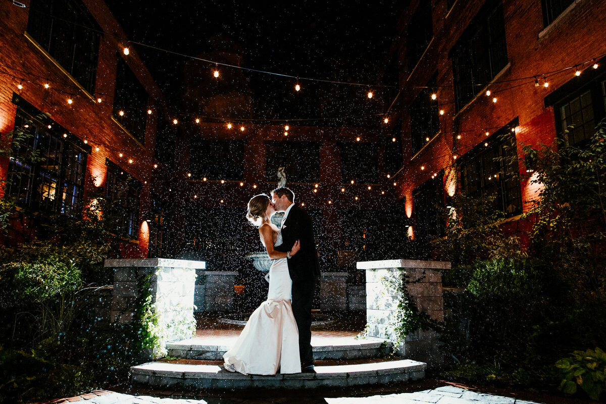 Bride and groom kissing outside in the rain with fairy lights in Buffalo, New York