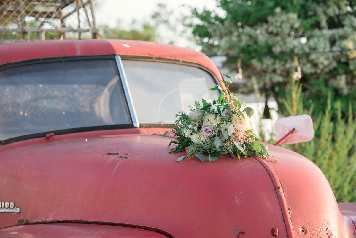 photo of bouquet on red car from wedding at The Loft by Bridgeview