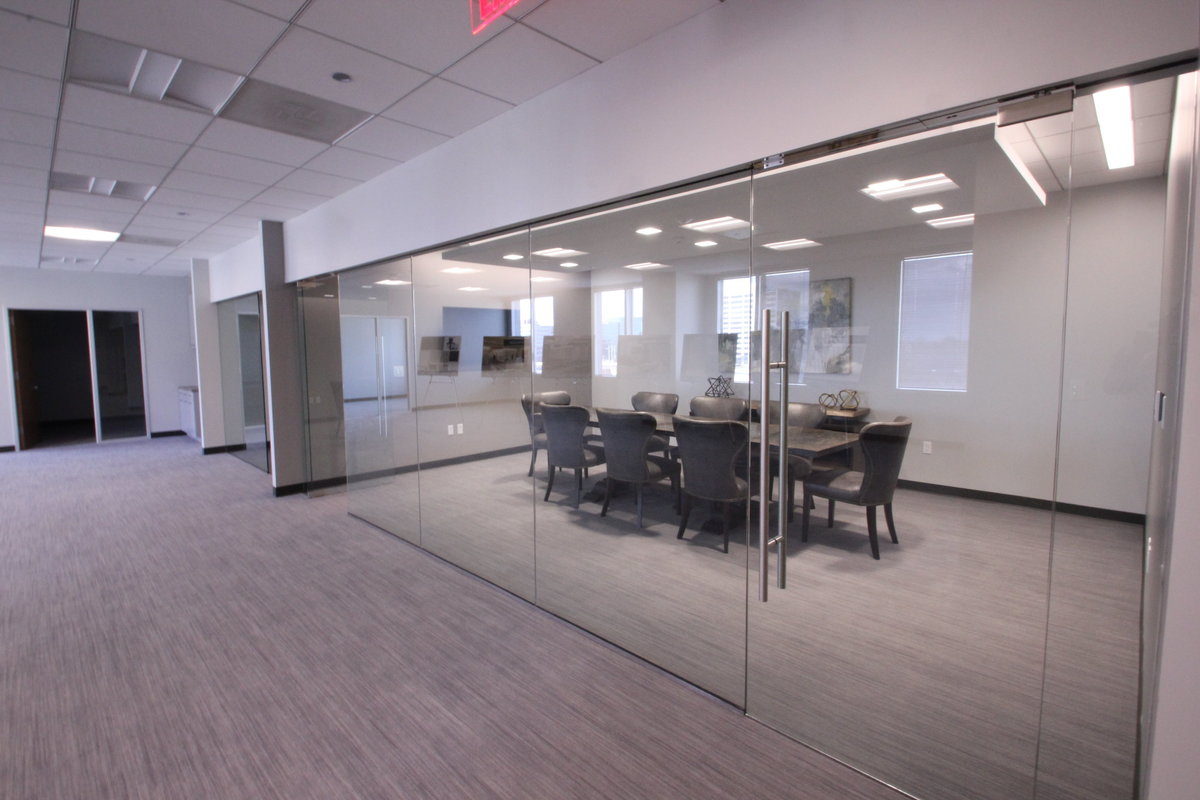 Glass doors and walls open up to commercial conference room.