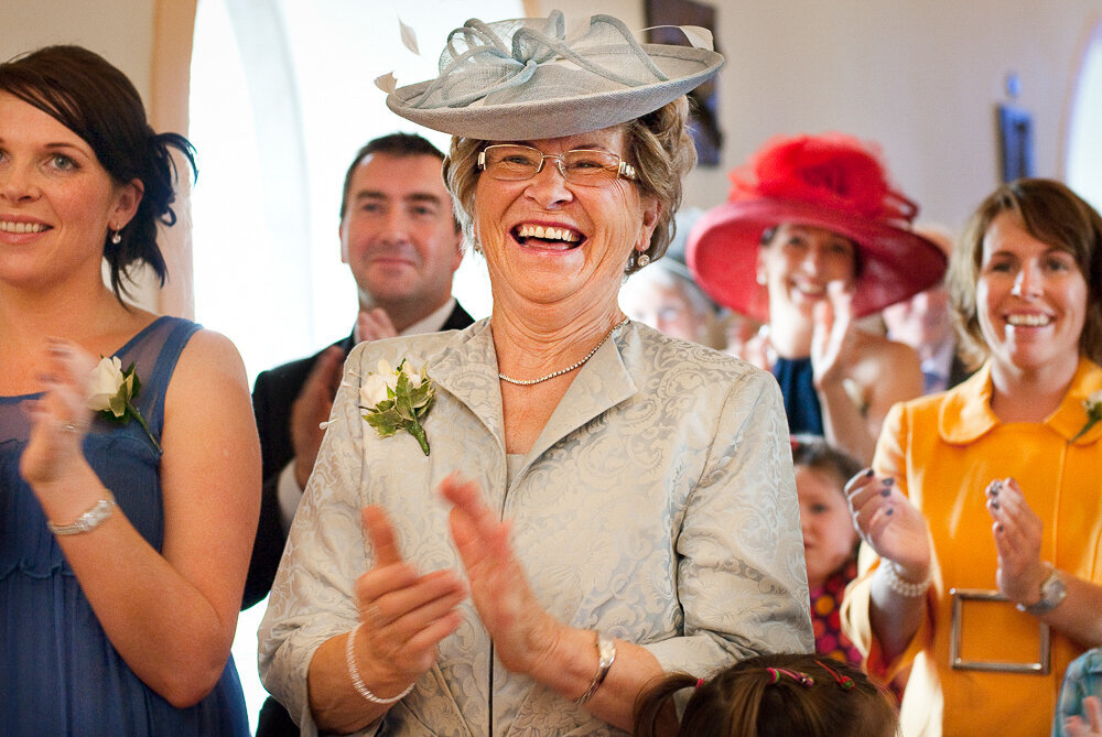 mother of the bride wearing a light, sage green outfit with matching hat clapping and laughing during wedding ceremony