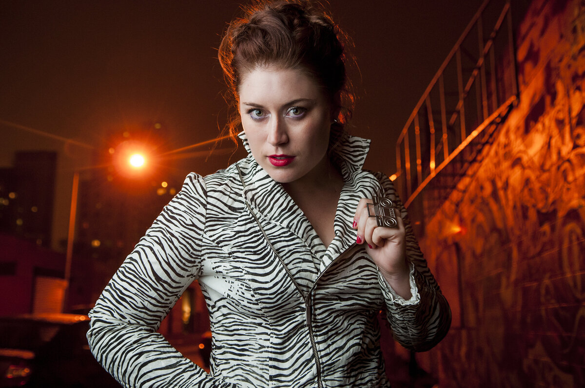 Red head woman with bright red lipstick poses on a city street for a photo a s she holds up the collar of a zebra printed jacket.