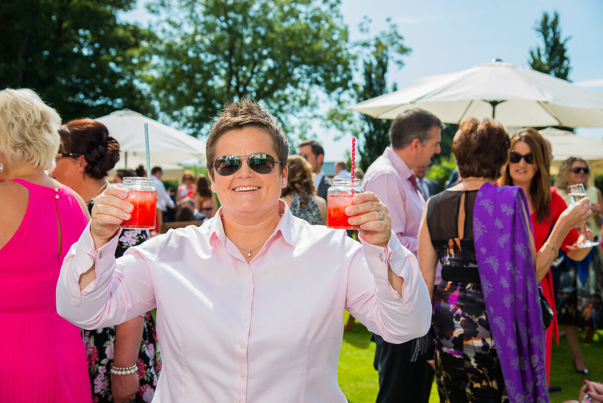 wedding guest holding colourful cocktails in garden