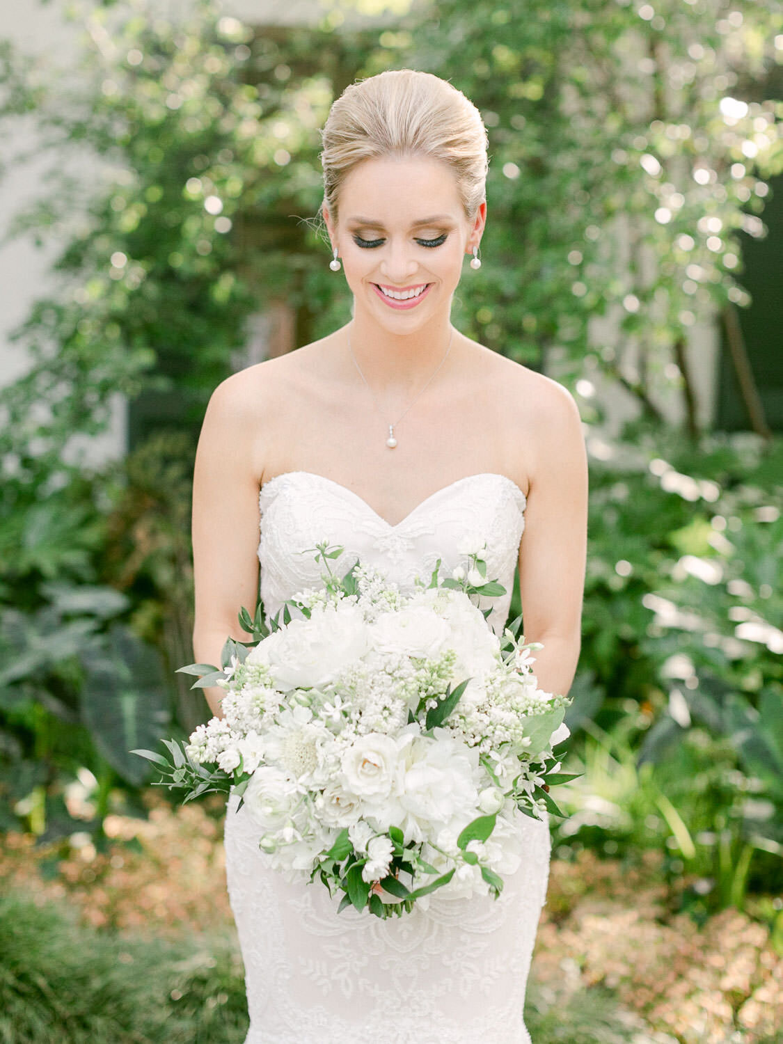 Bride holding white bouquet smiling in front of greenery at Dallas Arboretum Wedding