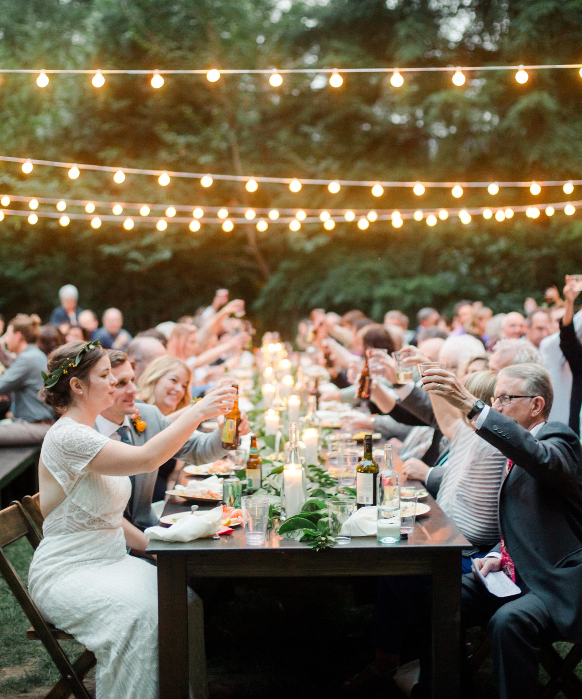 wedding guests cheers over reception table at wellspring spa wedding