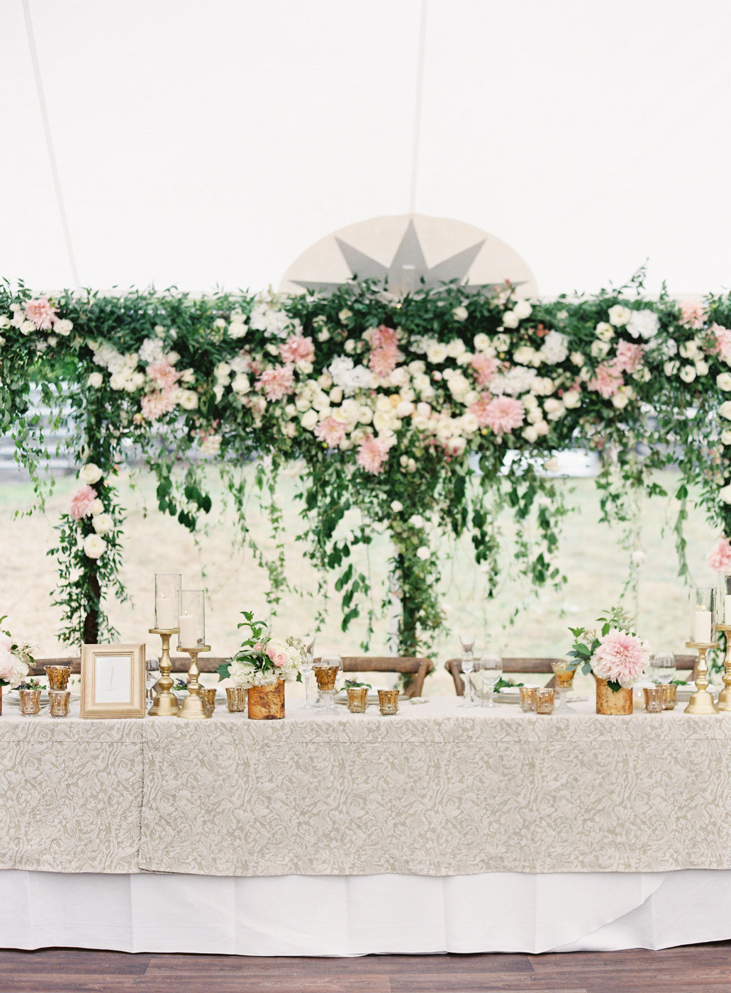Blush and greenery flower wall backdrop at summer tent wedding reception.