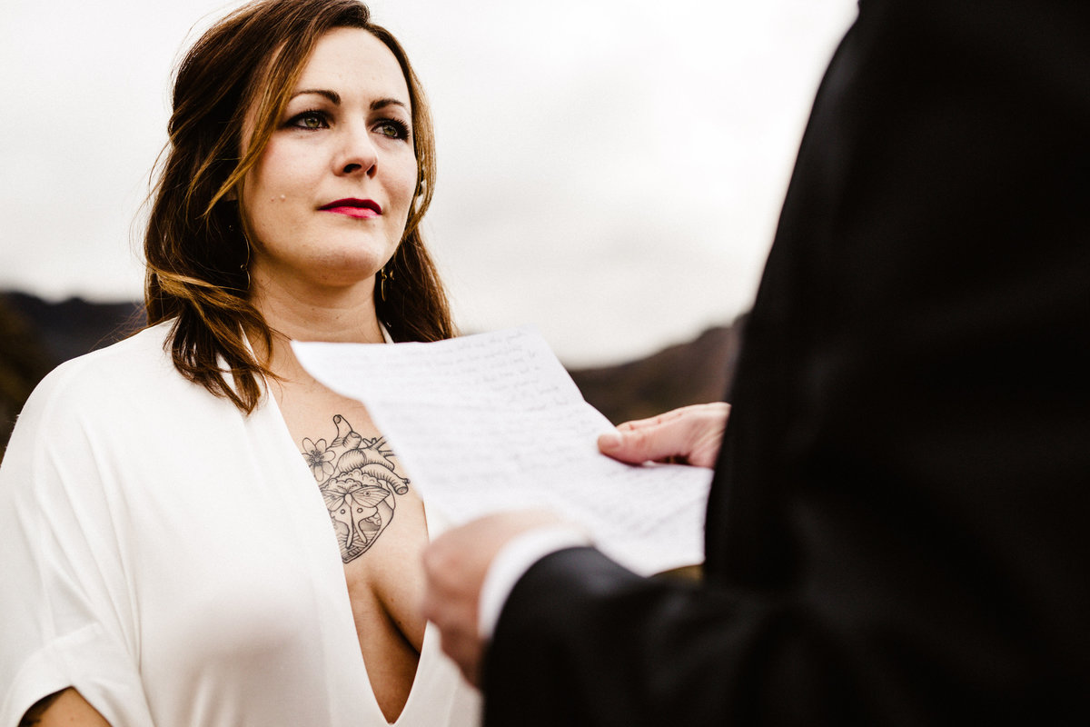 bride with chest tattoo holds back tears during elopement at hatcher pass