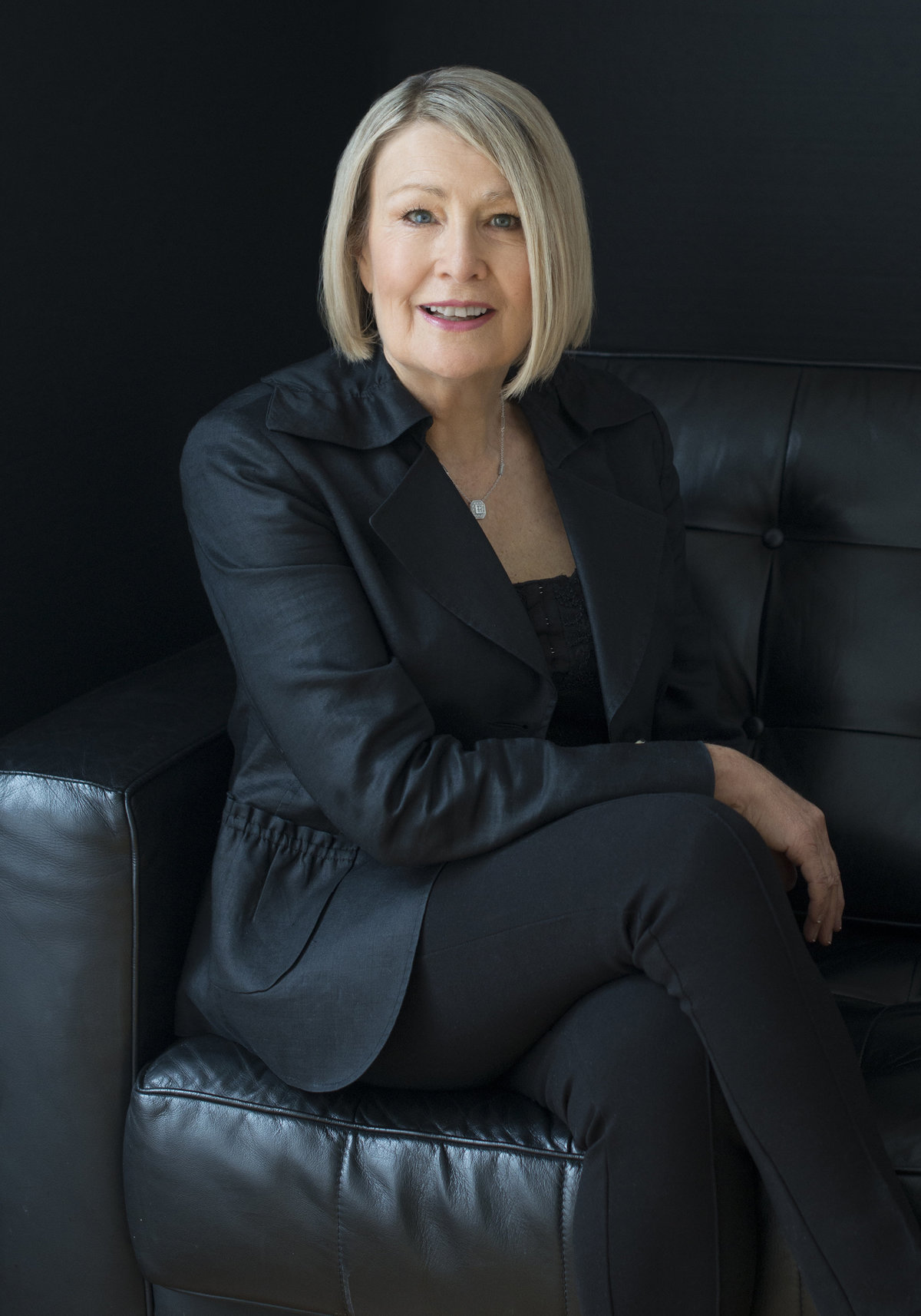 woman Ceo  headshot  photography by puja misra  specialist in womens  photography sitting on black couch wearing black formal  jacket