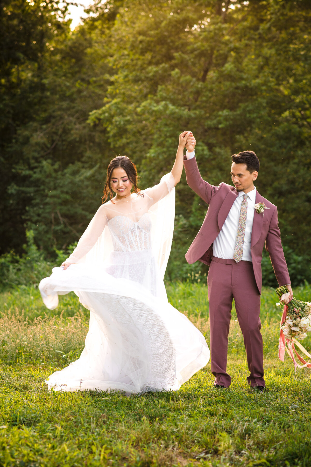 Asian bride and groom dancing outside