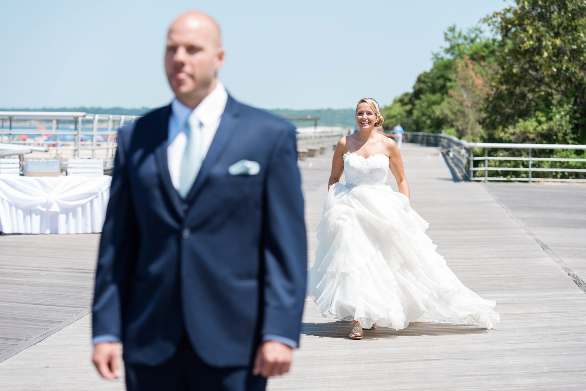 photo of bride and groom before the first look on the boardwalk for wedding reception at Pavilion at Sunken Meadow